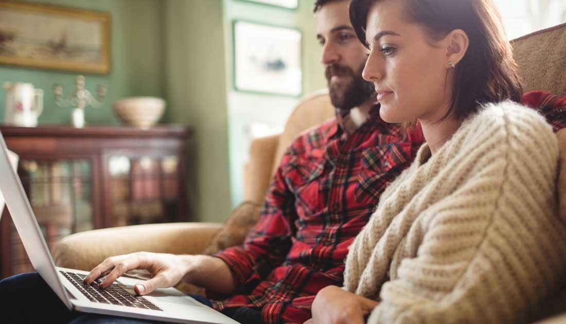 couple aussi sur un canapé devant un ordinateur