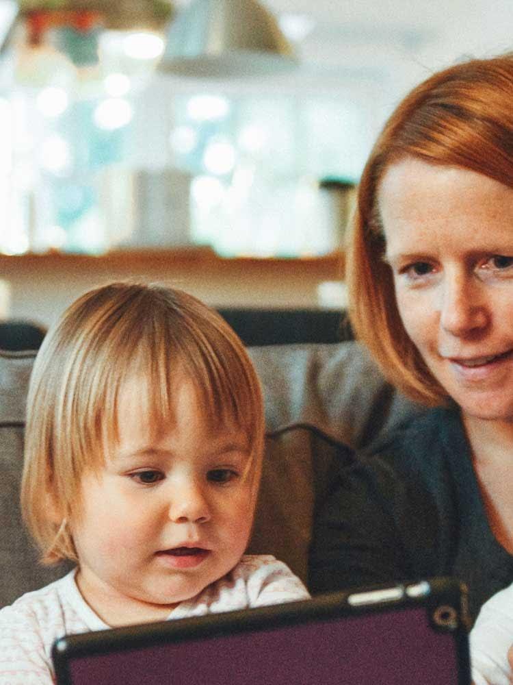une maman et son petit enfant regardant une tablette