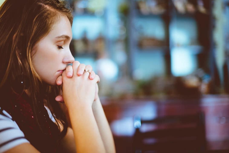 jeune femme en prière, mains jointes
