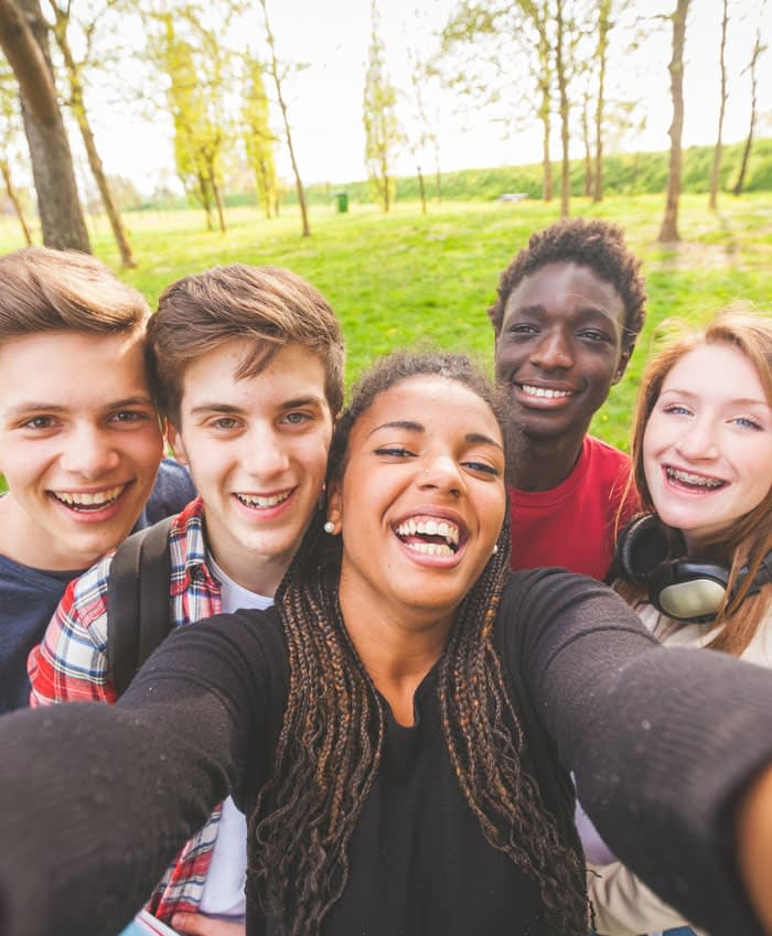 bande d'adolescents souriants se prenant en photo